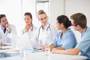 team av läkare och sjuksköterskor som diskuterar foto