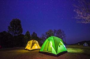 läger i skogen på natten med stjärnan foto
