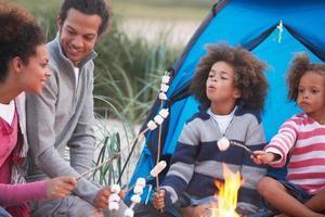 familjecamping på stranden och rostar marshmallows foto