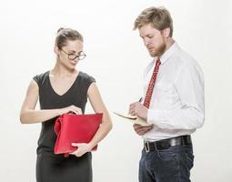 två kontorsarbetare som diskuterar affärsfrågor, foto