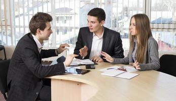grupp med tre personer som diskuterar foto