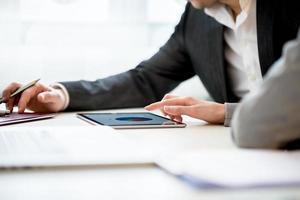 företagare diskuterar företag med hjälp av surfplatta foto