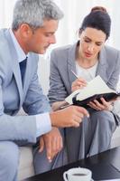 fokuserade affärsmän som arbetar och pratar tillsammans på soffan foto