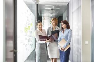 affärskvinnor med filmappar diskuterar i kontors korridor