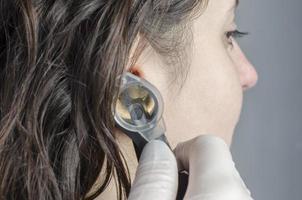 kvinnlig läkare som använder otoskop med en tjejpatient. foto
