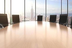 konferensrum med stort runt bord, stolar och utsikt över staden foto