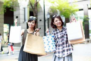 två unga kvinnor som shoppar tillsammans foto