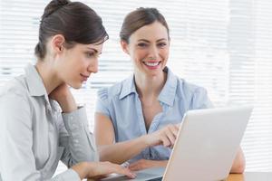 två leende affärskvinnor som arbetar på bärbar dator tillsammans