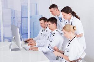 läkare som arbetar tillsammans på datorn på sjukhus foto