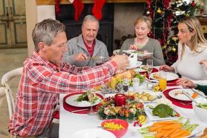 tre generationers familj som äter julmiddag tillsammans foto