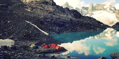 camping nära alpin sjö vintage effekt. färgglada tält. Kaukasusbergen. foto