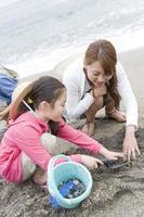 familj njuter av grävning av snäckskal foto