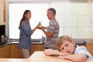 ledsen liten pojke som hör sina föräldrar argumentera foto