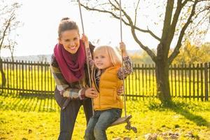 glad mamma svängande barn utomhus foto