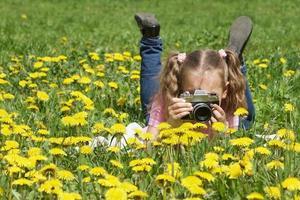 barn med en kamera i maskrosor