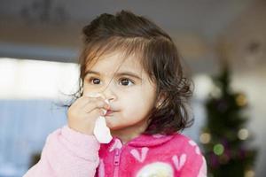 barn som rengör näsan med vävnad foto