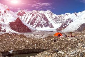campingplats på glaciärmoränen och snöbunden bergsutsikt som skiner foto