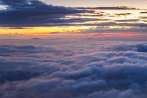 lager av berg och dimma vid solnedgången