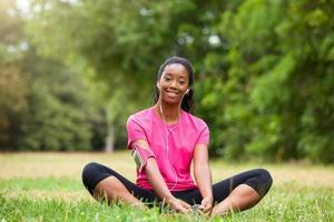 afroamerikansk kvinna jogger stretching - fitness, folk och foto