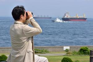 män i Japan med utsikt över havet med kikare