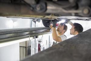underhållsingenjörer som reparerar bilen i verkstaden foto