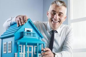 fastighetsmäklare med modellhus foto