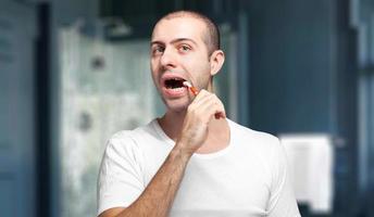 ung man som borstar tänderna foto