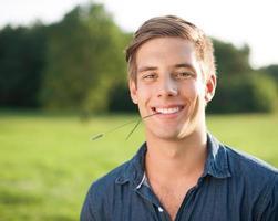 porträtt av en glad ung man i naturen som tuggar på