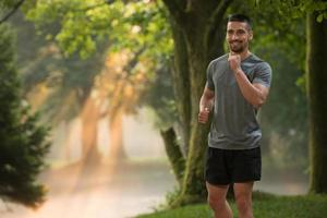 manlöpare som joggar utomhusträning i en park foto