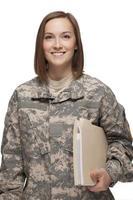 kvinnlig soldat som håller böcker foto