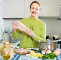 glad kvinnlig matlagning fisk foto