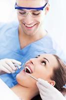 manlig tandläkare med kvinnlig patient foto