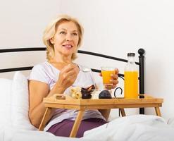 glad kvinnlig pensionär som äter frukost foto