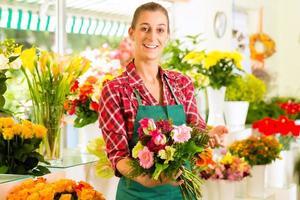 kvinnlig blomsterhandlare i blomsterbutik foto