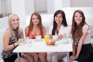 kvinnliga vänner som pratar över kaffe foto