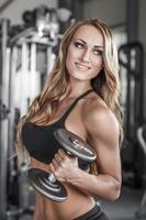 kvinnlig fitness modell poserar med hantel foto