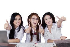 glada kvinnliga elever visar händer gest foto
