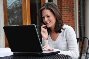kvinnlig student som använder dator och mobiltelefon foto