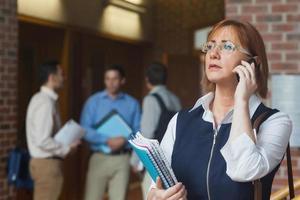 kvinnlig mogen student som ringer stående i korridoren foto