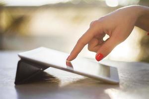 kvinnlig handklick på en digital surfplatta foto
