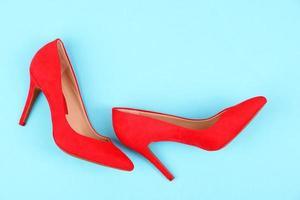 vackra röda kvinnliga skor, på blå bakgrund foto