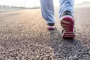 närbild av kvinnlig springa på vägen foto