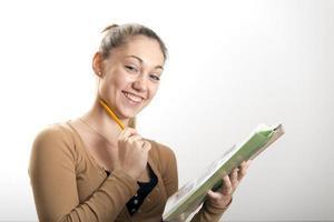 kvinnlig tonåring studerar med penna och bok foto