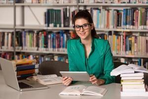 glad kvinnlig student med bärbar dator i biblioteket foto