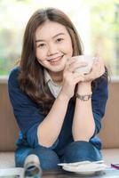 glad asiatisk le kvinnlig student som dricker kaffe foto