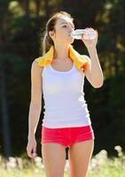 sportigt ungt kvinnligt dricksvatten efter träning foto