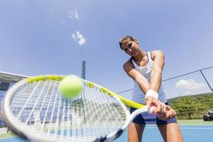 vacker kvinnlig tennisspelare i aktion foto