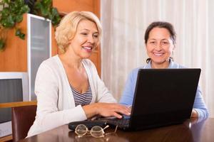 kvinnliga pensionärer med laptop inomhus foto