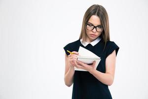 kvinnlig student som tittar på hennes anteckningsblock foto