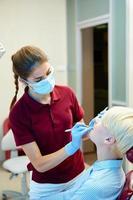 tandläkare som botar en kvinnlig patient foto